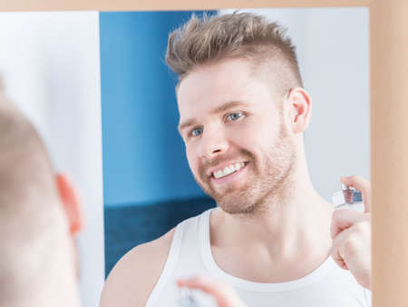 fascination: Photo of handsome happy man perfuming himself