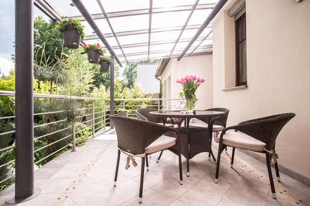 Foto nette rotan stoelen en tafel staan op terras Stockfoto