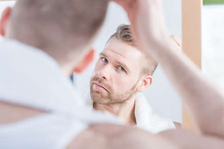 Image of handsome man watching himself in the mirror