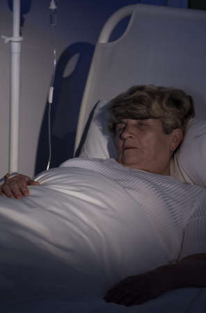 female catheter: Elderly woman lying in bed unconscious, vertical