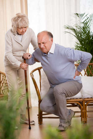 everyday people: Old woman is helping her husband to stand up Stock Photo