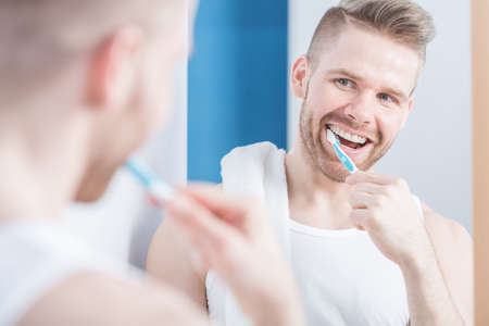 white man: Photo of young fashionable man brushing teeth