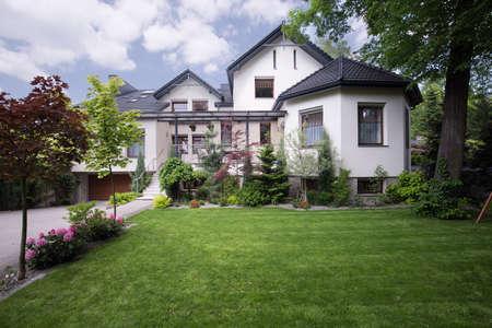庭の草の前で白い家の外観