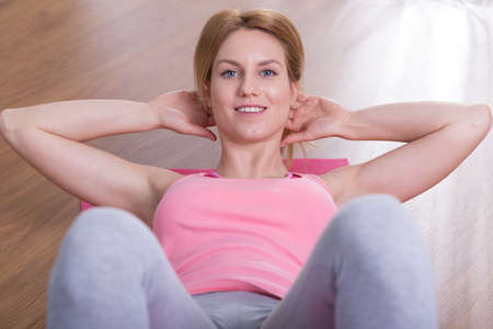 situps: Young woman is doing sit-ups at home