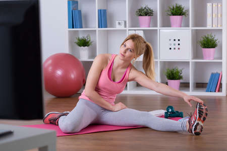 doing: Young woman is doing stretching exercise at home