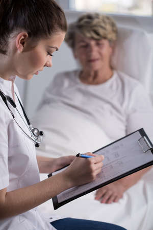 old and young: Doctor is checking her patient test results