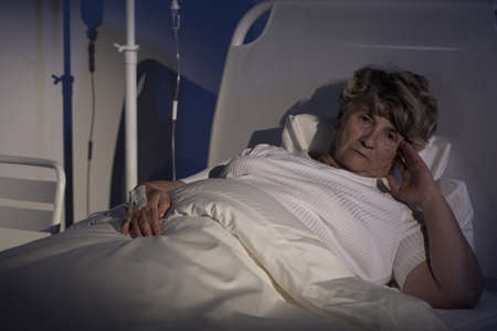worrying: Female patient lying in bed and worrying about her health Stock Photo
