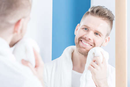 narcissistic: Picture of handsome smiling male drying face with towel