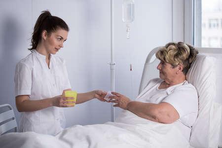 female catheter: Young nurse is giving medicine to elder patient Stock Photo