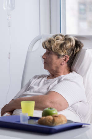 female catheter: Elderly woman in hospital is not interested in her food Stock Photo