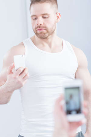 narcissistic: Image of handsome muscular man taking photo of himself Stock Photo