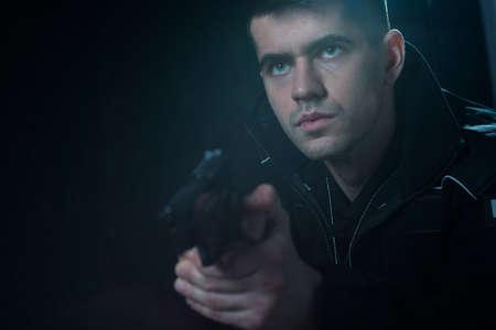 criminal: Cop holding pistol and aiming at criminal Stock Photo