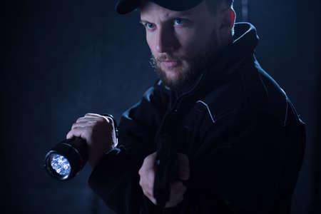 officier de police: Portrait d'un policier utilisant une lampe de poche lors de l'action