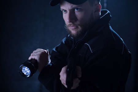security uniform: Portrait of policeman using flashlight during action