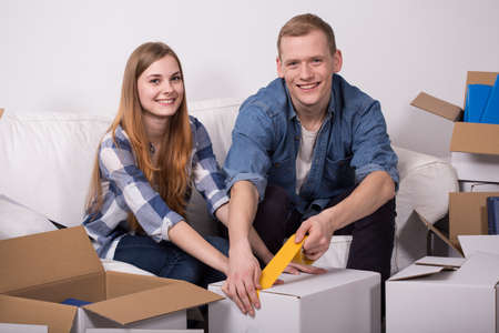 moving box: Young couple is taping the box during moving out Stock Photo