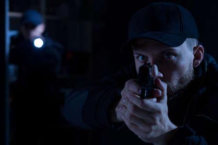pointing gun: Adult police officer pointing gun at criminal
