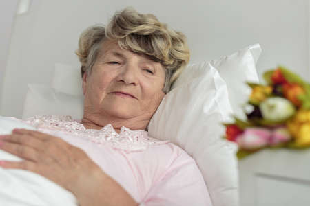 bunch of flowers: Woman in hospital looking on flowers bouquet