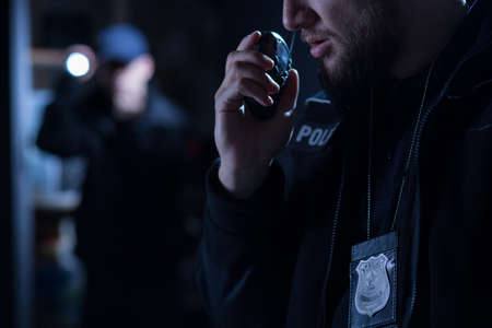 policier: Officier utilisant talkie-walkie lors de l'intervention de la police