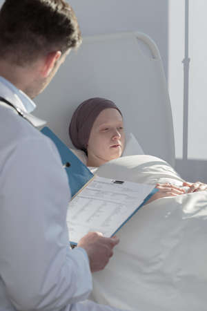 informing: Doctor is informing his patient about results of medical exams