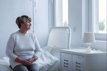 Ziek eenzame vrouw zitten op ziekenhuis bed Stockfoto