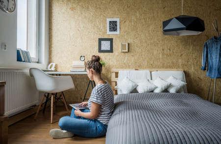 Tiener meisje zittend op de vloer in haar slaapkamer