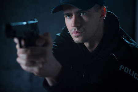 offender: Young policeman with pistol aiming at offender Stock Photo