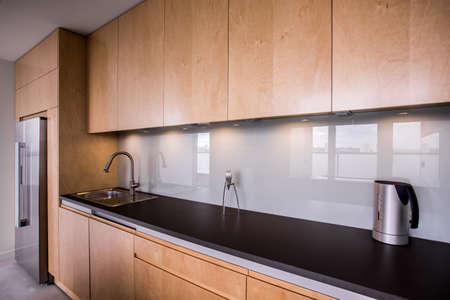 kitchen cupboard: Wooden cupboards and black worktop in modern kitchen