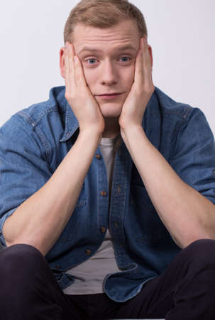 bothered: Young man is worried about moving out Stock Photo