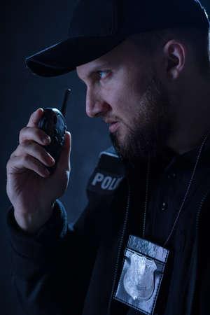 shortwave: Portrait of angry policeman using walkie talkie