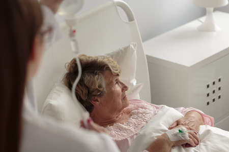 Ill senior woman during treatment in hospital