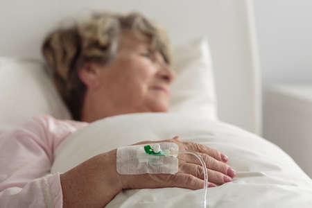 an elderly person: Jubilado femenino enfermo acostado en la cama de hospital