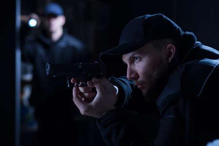patrol officer: Police officer holding handgun during police intervention