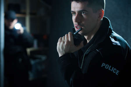 talkie: Policeman at action talking on walkie talkie Stock Photo