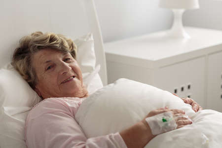 inpatient: Smiling senior woman lying in hospital bed