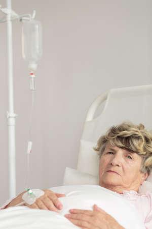 mujer descansando: Mujer mayor enferma que se reclina en cama de hospital