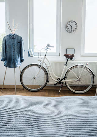 stylish women: Modern bicycle and denim shirt in the bedroom