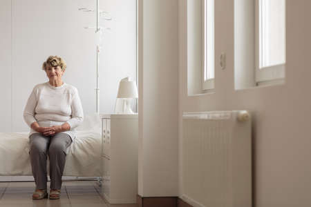 inpatient: Elder lady sitting on the bed in hospital room Stock Photo