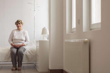 persona sentada: Elder señora sentada en la cama en la habitación del hospital Foto de archivo