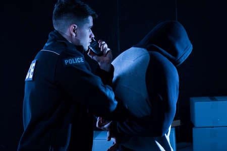 Mature policeman arresting law-breaker at night