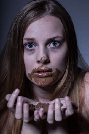 gorging: Close up of a thin frightened teenager gorging on chocolate Stock Photo