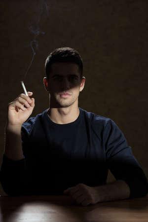 nicotine: Young man addicted to nicotine smoking a cigarette
