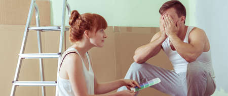 redecorating: Young couple is redecorating walls in flat