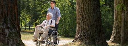 helping: El hombre joven está ayudando a su abuelo en el parque Foto de archivo