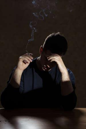 joven fumando: Imagen de hombre de la desesperación que fuma un cigarrillo