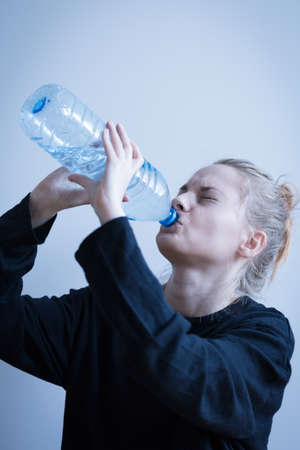 regain: Image of a woman with eating disorder drinking water Stock Photo