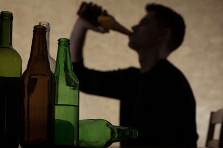 Alcoholism among young people - teenager drinking beer Stock Photo