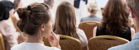 De jonge vrouw luistert op de conferentie