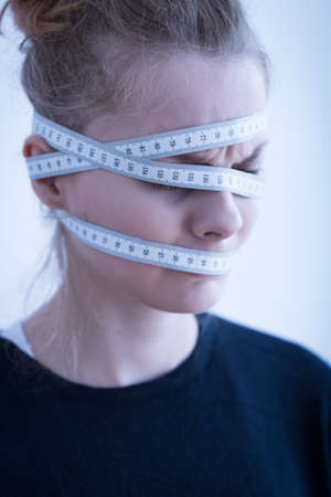 mental disorder: Close up of an anorexic female with tape-measure around head