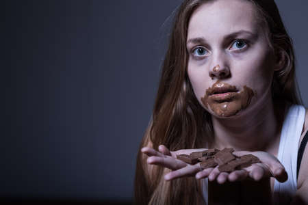 gorging: Photo of sick skinny girl with dirty mouth from chocolate Stock Photo