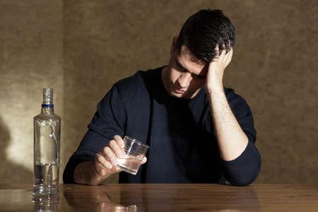 tomando alcohol: Joven vodka hombre beber en el vaso